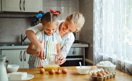 Happy family mother and child daughter bake kneading dough in the kitchen