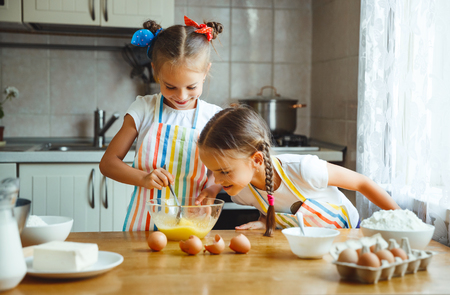 christmas baker's: happy sisters children girls bake cookies, knead dough, play with flour and laugh in the kitchen