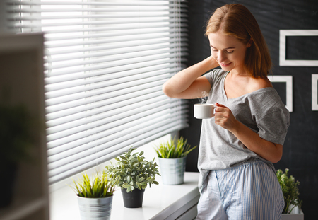 Happy young woman drinks coffee in bed at window in morning Stock Photo