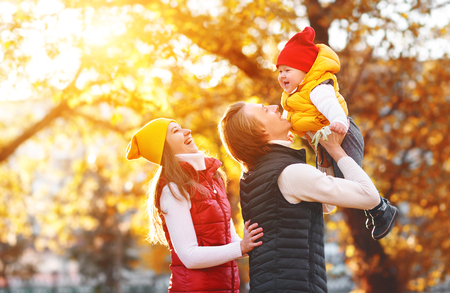 happy family mother father and baby on   autumn walk in the park