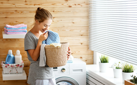 a Happy housewife woman in laundry room with washing machine Фото со стока