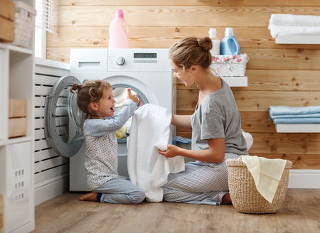 Happy family mother housewife and child daughter in laundry with washing machine Stock fotó