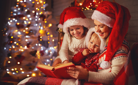 happy family mother and children read a book at christmas near   fireplace at home