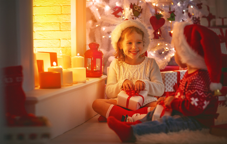 happy children with christmas presents near a Christmas tree and a fireplace