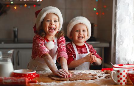 面白い顔の子供がクリスマスのクッキーを焼く幸せ