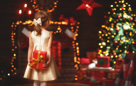 happy   child girl   back with christmas gift at evening home