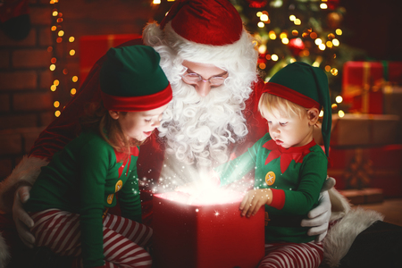 Santa Claus and little elves with a magic gift for Christmas Stock Photo
