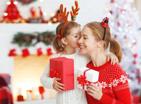 Mère heureuse mère et fille donnant cadeau de noël et s & # 39 ; embrasser Banque d'images - 89274064