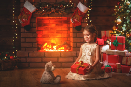 happy   child girl with christmas gift at evening home  Stock Photo