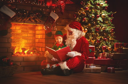 santa claus reads a book to a little elf by fireplace and Christmas tree
