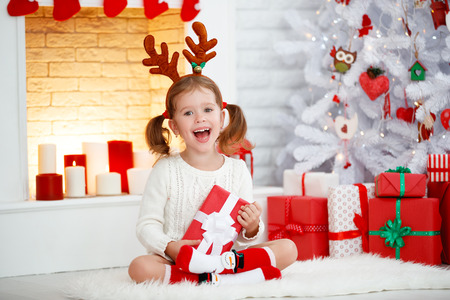 happy laughing child girl with gift in morning at Christmas tree