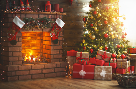 interior christmas. magic glowing tree, fireplace and gifts Imagens