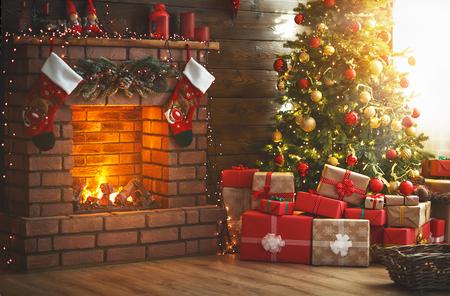 Navidad interior. Árbol mágico resplandeciente, chimenea y regalos. Foto de archivo