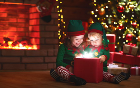 Christmas. elves with a magic gift near Christmas tree and a fireplace