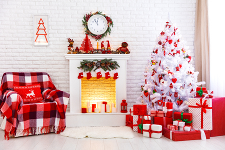 Christmas interior in red and white colors with Christmas tree and fireplace