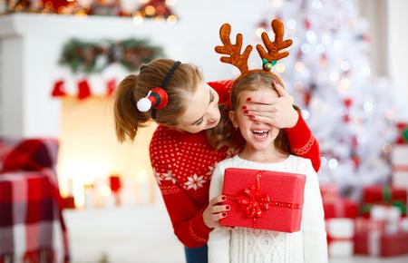 szczęśliwa rodzina matka i córka dając prezent na Boże Narodzenie i ogarnięcie