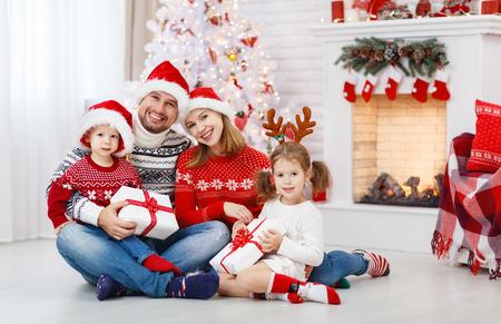 szczęśliwa rodzina, ojciec, matka i dzieci w domu na Boże Narodzenie rano
