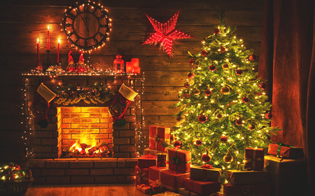 interior christmas. magic glowing tree, fireplace gifts in  dark at night Stockfoto