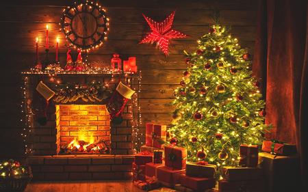interior christmas. magic glowing tree, fireplace gifts in  dark at night Archivio Fotografico