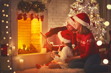 happy family father mother and children sitting by fireplace on Christmas Eve Stock Photo
