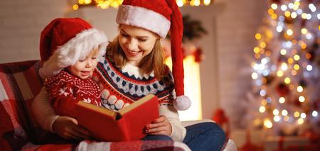 Véspera de Natal. mãe de família e bebê lendo livro mágico em casa perto da lareira e da árvore de natal