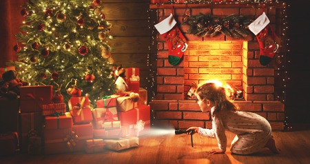 Christmas night. baby girl with a flashlight at night looking for gifts under a Christmas tree Imagens