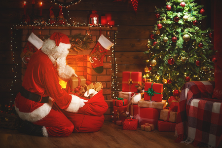 Merry Christmas! santa claus near the fireplace and Christmas tree with gifts