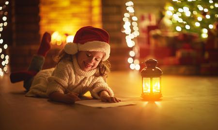 Niño, niña, escritura, carta santa, hogar, cerca, el, árbol de navidad Foto de archivo - 90434219