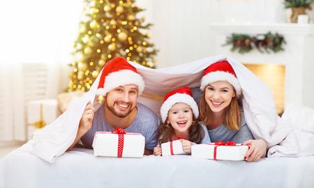 행복 한 가족 어머니 아버지와 아기 잠 옷에 침대에서 크리스마스 아침에 아이 선물을 엽니 다 스톡 콘텐츠