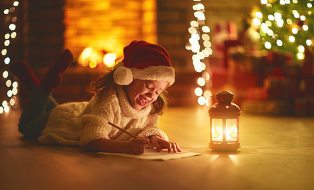 child girl writing letter santa home near the Christmas tree