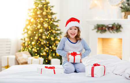 happy funny child girl  with gifts  in bed on Christmas morning Stock Photo