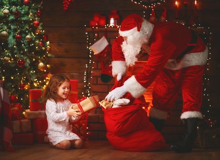 Merry Christmas! santa claus and little child girl at night at the Christmas tree Stock Photo
