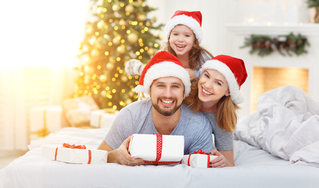 happy familymother father and child on Christmas morning in bed in pajamas open gifts