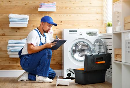 working man plumber repairs a washing machine in   laundry Zdjęcie Seryjne