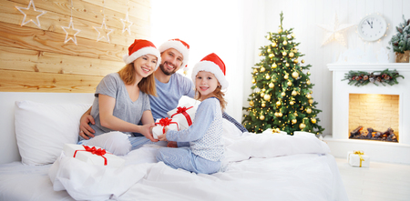 happy family mother father and child on Christmas morning in bed in pajamas open gifts
