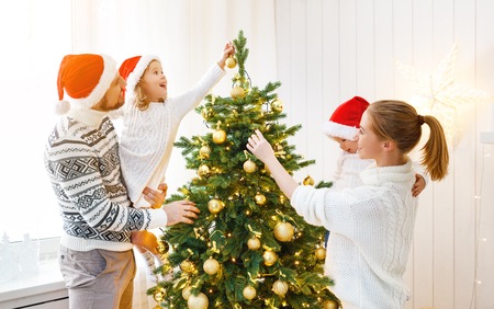 happy family mother father and children decorating a Christmas tree at home