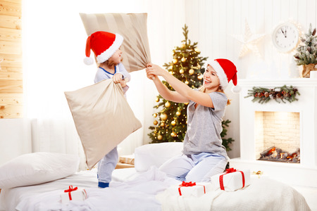 happy family mother and child daughter at christmas morning playing and fighting pillows in bed