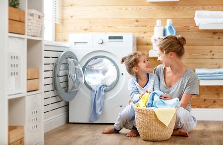 Famiglia felice madre casalinga e figlia del bambino in lavanderia con lavatrice