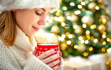 happy woman with a mug of tea near a Christmas tree