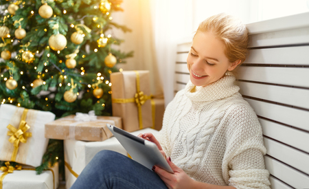 happy woman with with tablet pc at morning near a Christmas tree