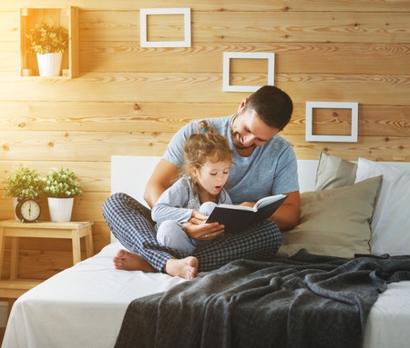 happy family father and child daughter reading book in bed Foto de archivo