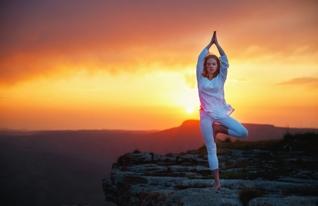 woman practices yoga and meditates   on sunset mountains, peak