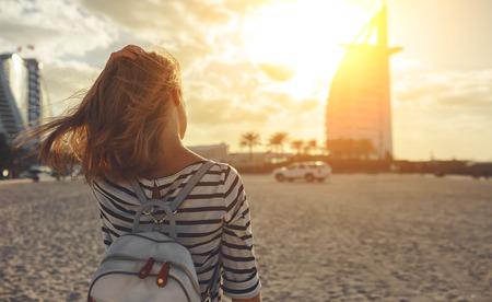 happy young woman enjoying freedom with open hands on sea at Burj Al Arab, hotel in Dubai United Arab Emirates UAE, January 2018
