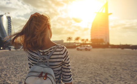 happy young woman enjoying freedom with open hands on sea at Burj Al Arab, hotel in Dubai United Arab Emirates UAE, January 2018