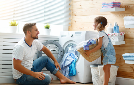 洗濯機で洗濯中の幸せな家族の男の父の家主と子供の娘