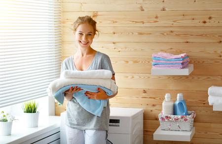 Kobieta szczęśliwa gospodyni domowa w pralni z pralką