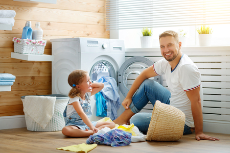 Happy family man father  householder and child daughter in laundry with washing machine  Standard-Bild