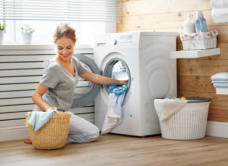 a Happy housewife woman in laundry room with washing machine 版權商用圖片 - 93867833