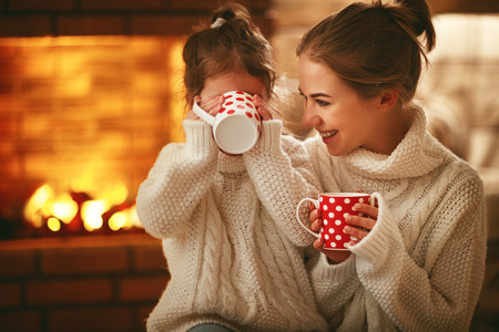 family mother and child daughter drinking tea and laughing on winter evening by fireplace Imagens - 93867849