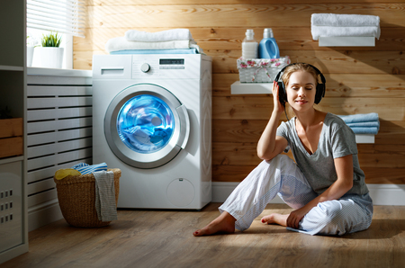 a Happy housewife woman listens to music on headphones in laundry room with washing machine   Banque d'images